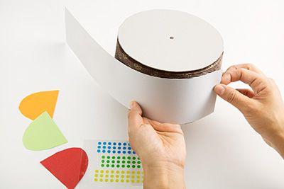シフォンケーキ型に合わせて切った厚紙を、上面と側面に両面テープで貼り、ハットのベースをつくる。