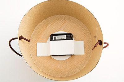 時計を分解し、電池と秒針部分を取り出し、ハットの上部に取り付ける。時計を分解しているところ