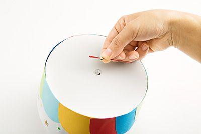 針の先を折って、画用紙でつくった数字(年齢)をテープでつける。ハットの上部にとりつけているところ