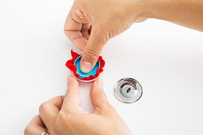 くるみボタンキットを使って、赤いフェルトのくるみボタンをつくり、トップに縫い付ける。