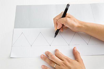 厚紙の裏面に型紙を置いて、型紙のラインに沿ってボールペンでスジをつける。