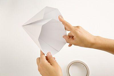 2枚の画用紙を使って円すいをつくる。一片を両面テープで留めて、もう一片は子どもの頭のサイズに合わせて調整し、余った部分は切り、両面テープで貼り付けてハットのベースをつくる。この上にカラーコピーした絵を貼り付けるので、多少仕上がりが汚くてもOK。
