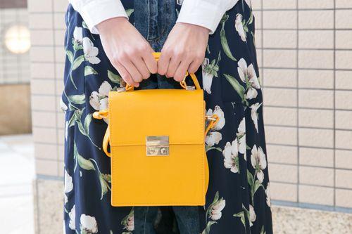 モノトーン調にまとめたスタイルに、イエローのワンポイントが映えるグッドチョイスなハンドバッグ!