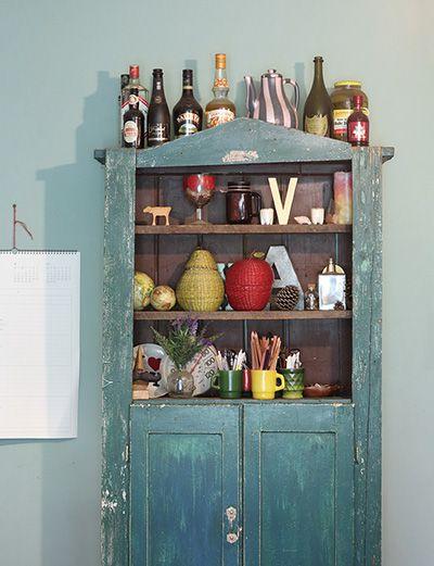 古い外国のアンティーク棚に食器や色鉛筆などを収納。