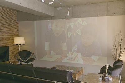 リビングの白壁をスクリーンに、プロジェクターで家族写真やDVDを映写。大切な家族だんらんのひととき♪