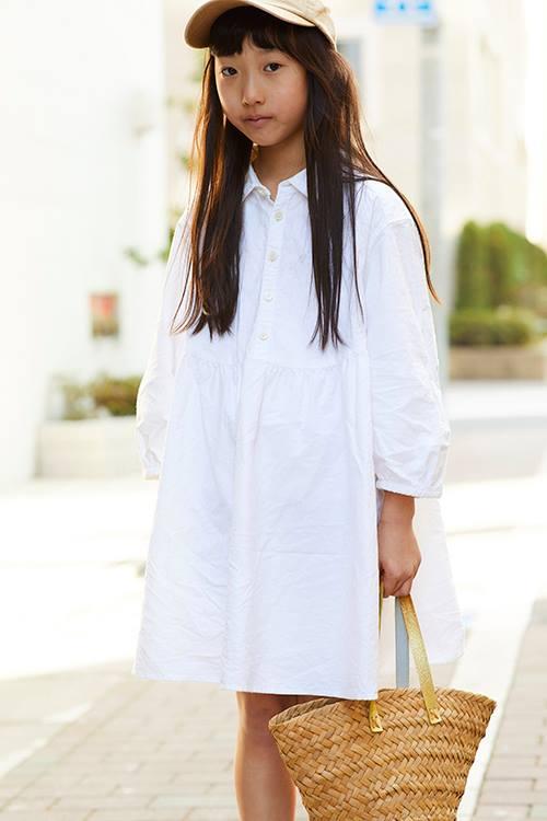 girlは白のワンピースを主役にした清楚な装い。<br /> ベージュのキャップやカゴバッグがアクセント。&#8221; /></p> <p class=