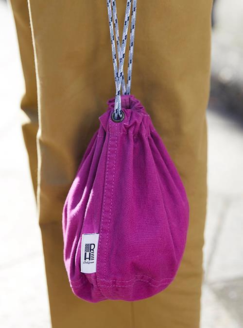 パープルの巾着バッグがコーデにアクセントをプラス!