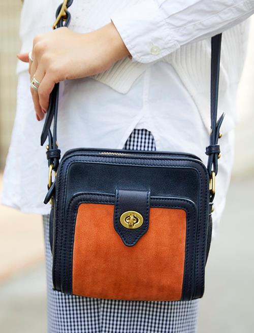 ネイビー×オレンジのレトロなショルダーバッグを合わせて、クラシカルなムードに。
