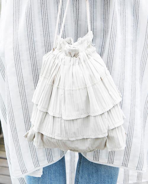 フリルがあしらわれた巾着バッグを選んでトレンド感を後押し!/></p> <p class=
