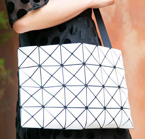 三角ピースが規則的に並んだデザインのバッグを選んでモードな印象にまとめ。
