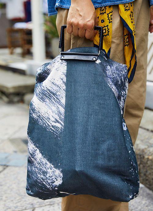 ダークトーンのバッグを選んで落ち着きのある雰囲気に仕上げ。