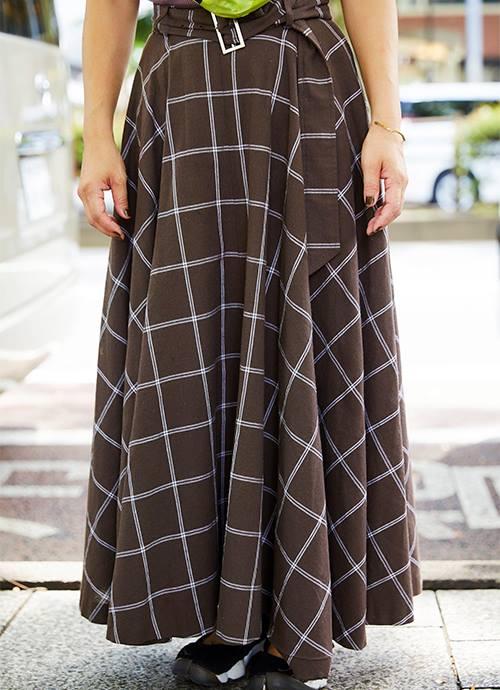 ブラウンのチェック柄スカートを合わせて落ち着きのあるムードにまとめ。/></p> <p class=