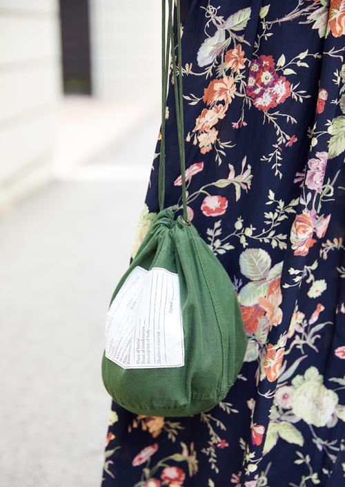 ヴィンテージの巾着バッグがこなれた雰囲気
