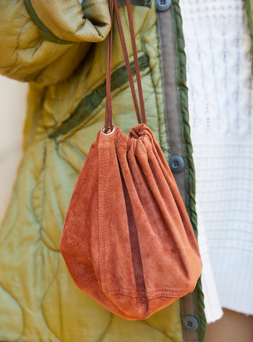 スウェードの巾着バッグがニュアンスをプラス。