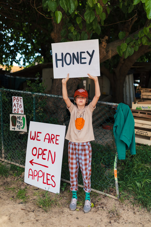 ボボショーズのオレンジのTシャツを着た少年がhoneyの看板を持っている