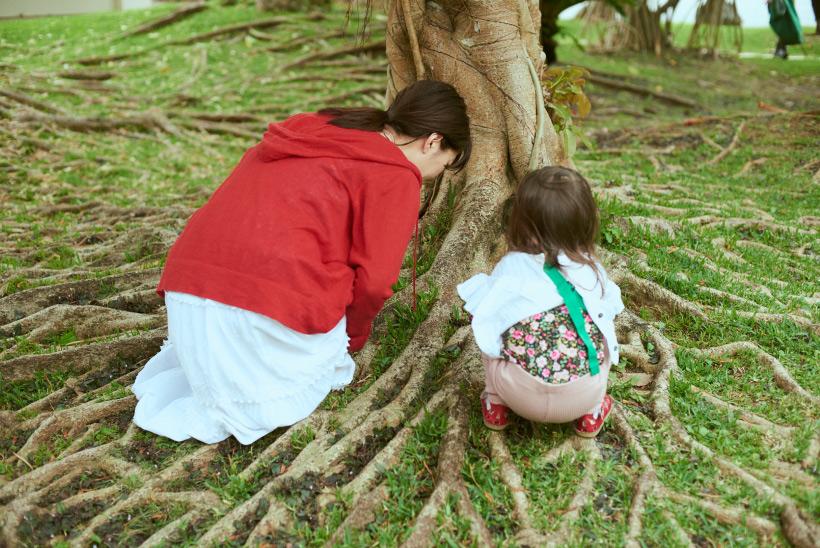 木の根を観察する坂本美雨さん親子